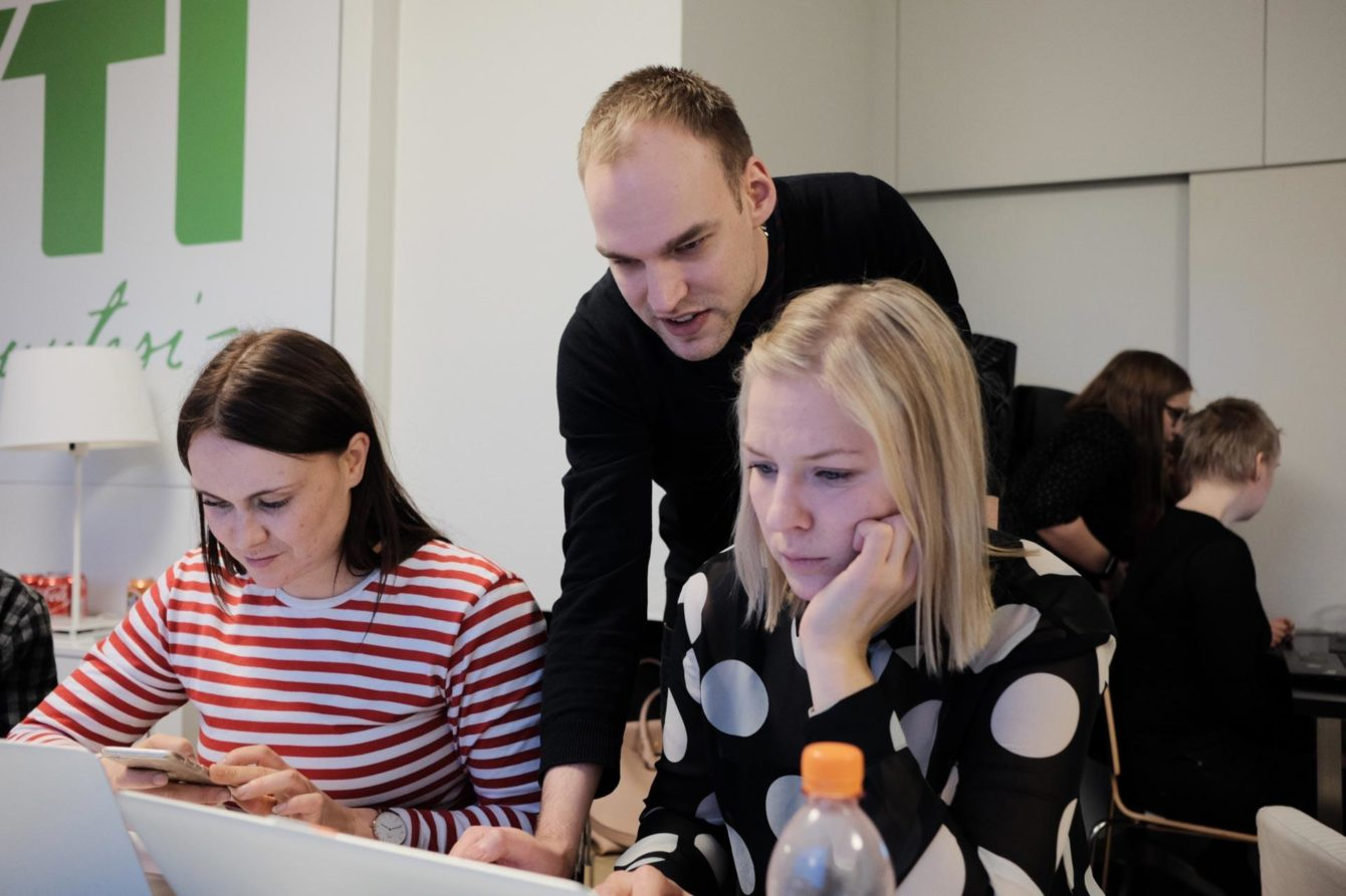 Jan Lindström helping two female coders