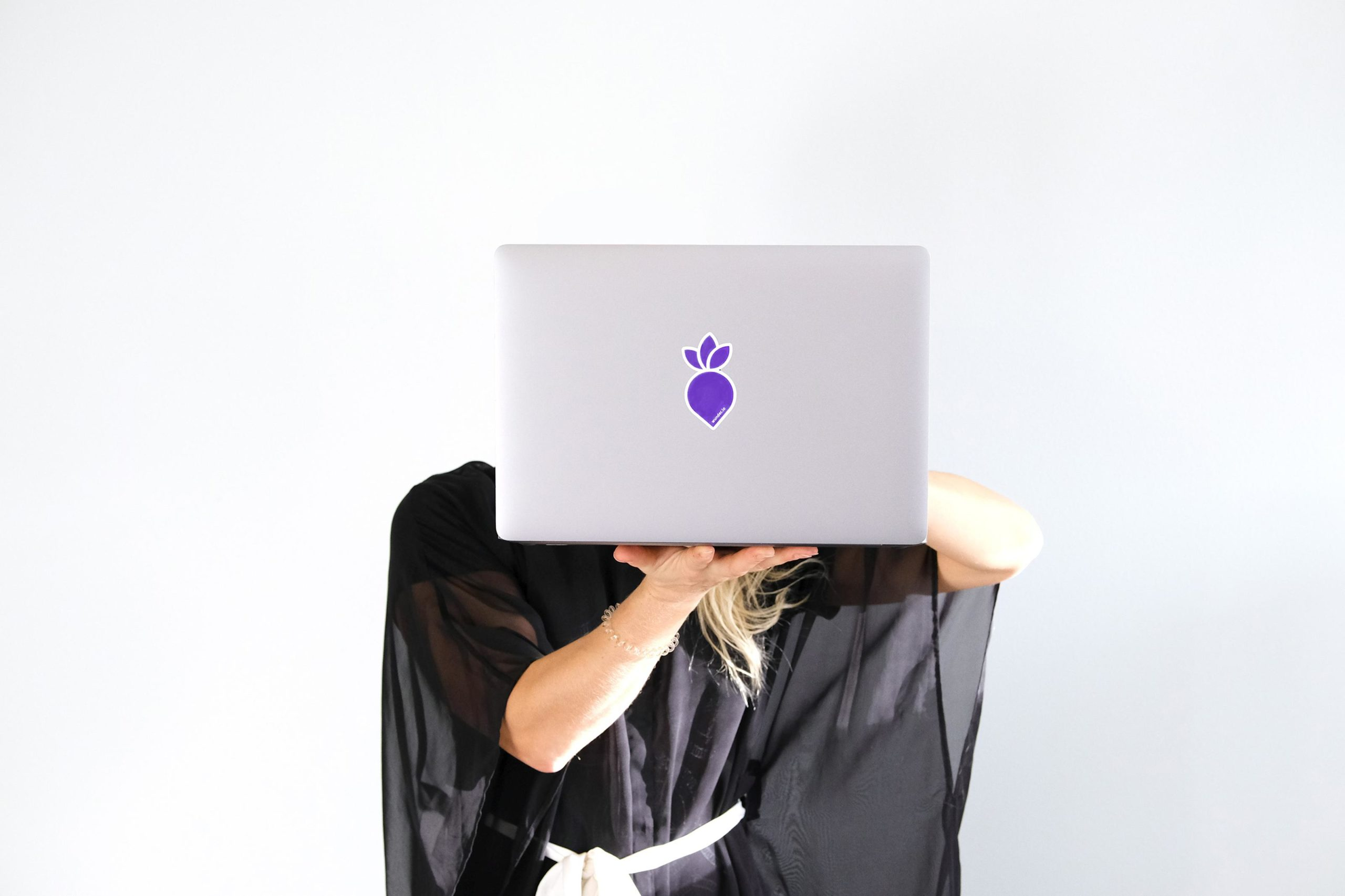 Person holding laptop with one hand in front of they face